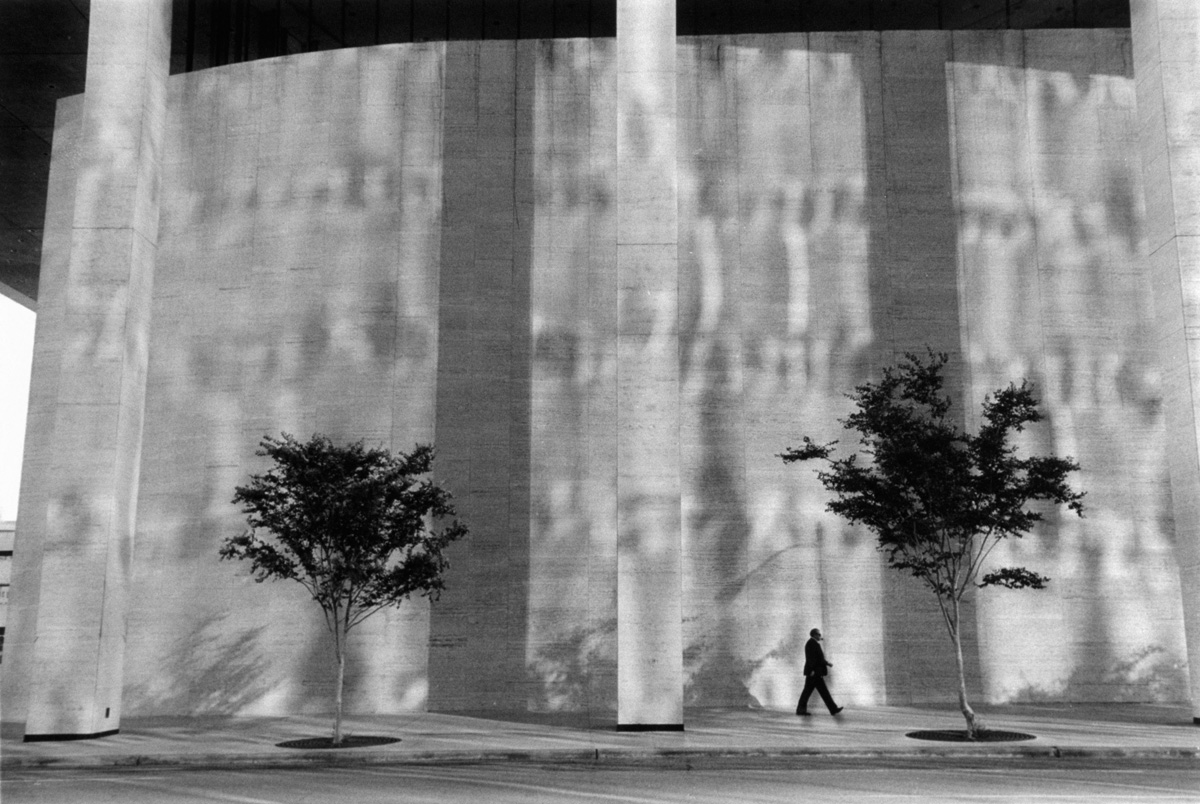 Man walking in front of building Houston, undated