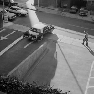 Man walking past parking lot